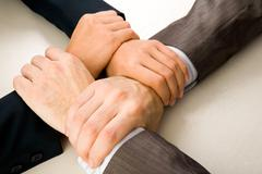 Image of crossed hands of business partners Stock Photos