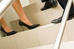 Image of female and male legs standing on marble ladder at meeting Stock Photos