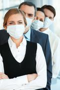 Pretty female in protective mask looking at camera with row of partners behind Stock Photos