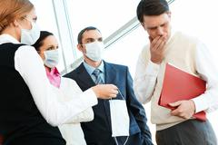 Group of associates in protective masks giving one to sick man Stock Photos
