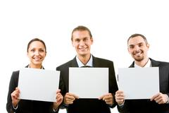 Row of happy business partners holding blank papers and looking at camera Stock Photos