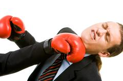 Portrait of defeated businessman in boxing gloves being hit by opponent Stock Photos