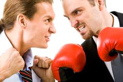 Portrait of aggressive businessmen in boxing gloves looking at each other with a Stock Photos