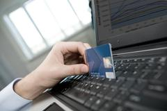 close-up of human hand over laptop keyboard with plastic card - stock photo