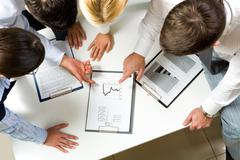 above view of friendly workteam discussing business-plan - stock photo