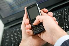 photo of male hand holding cellular phone and pressing its buttons - stock photo