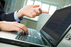 close-up of male hand with forefinger pointing at laptop screen on workplace - stock photo