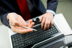 above angle of male hand with pen pointing at laptop screen during discussion - stock photo