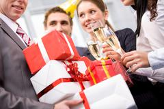 Image of wrapped giftboxes in male hands with cheering friends on background Stock Photos