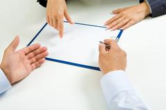 close-up of people hands during discussion of business-plan - stock photo