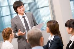 photo of confident businessman explaining activities to his colleagues in office - stock photo