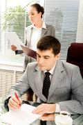 portrait of serious boss signing contract with executive secretary on background - stock photo