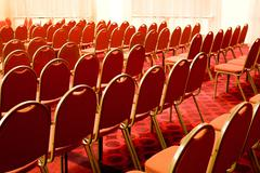 image of rows of red armchairs in conference hall - stock photo