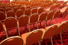 Stock Photo of back view of several rows of red armchairs in conference hall