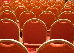 Stock Photo of rear view of several rows of red armchairs in conference hall
