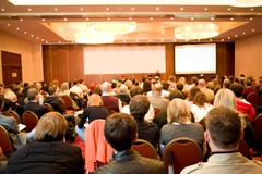 Rear view of many listeners sitting on chairs during lecture at conference Stock Photos
