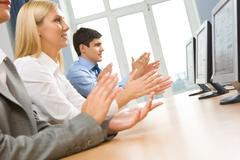row of happy business partners applauding at conference - stock photo
