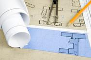 Stock Photo of close-up of blueprints with sketches of projects on workplace and some mechanica
