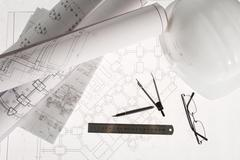 Stock Photo of close-up of blueprints with sketches of projects, eyeglasses, helmet and some me
