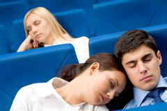 group of business partners dozing in arm-chairs during presentation - stock photo