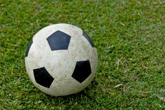 old soccer ball on green grass - stock photo