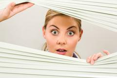 Portrait of surprised woman looking at camera out of venetian blind Stock Photos