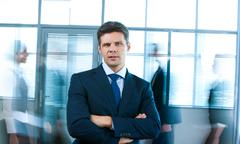 Portrait of confident man looking at camera in office with busy people passing b Stock Photos