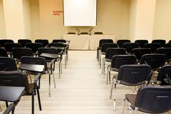 image of several rows of armchairs in conference hall - stock photo