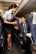 Kind stewardess giving glass of water to young businessman in airplane Stock Photos