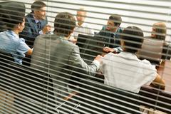 View from behind venetian blind of associates interacting at working meeting Stock Photos