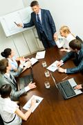 Above angle of business people listening to confident man during seminar Stock Photos