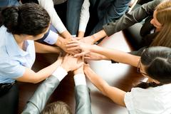 Above angle of business partners making pile of hands on workplace Stock Photos