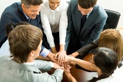 Photo of happy business partners making pile of hands on workplace Stock Photos
