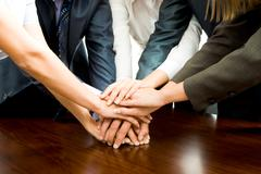 close-up of business people's hands on top of each other - stock photo