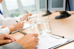 Image of human hand holding pen and making notes with glass of water and monitor Stock Photos