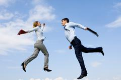 Portrait of happy partners jumping against blue sky Stock Photos