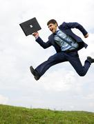 Well-dressed leader leaping over green grass with cloudy sky at background Stock Photos