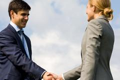 Photo of business partners handshaking on background of cloudy sky Stock Photos