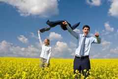 portrait of happy business partners enjoying life and freedom in yellow field - stock photo