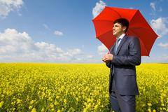 Image of young businessman with red umbrella in flower field Stock Photos