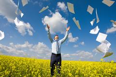 Image of happy winner throwing papers in yellow meadow Stock Photos
