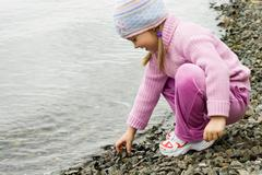 Pretty girl in violet clothes touching pebbles by the river Stock Photos