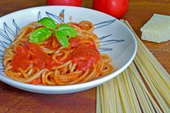 spaghetti with ingredients around - stock photo