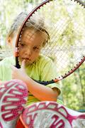 sad child with tennis racket looking through its net outdoors during vacation - stock photo