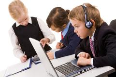 Photo of serious businesschild with headset looking attentively at laptop screen Stock Photos