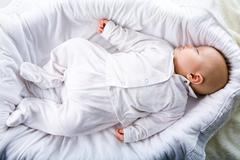 Above view of fragile baby having a nod in comfortable cradle at home Stock Photos