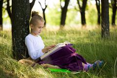 Pretty girl sitting under tree and reading at summer in a park Stock Photos