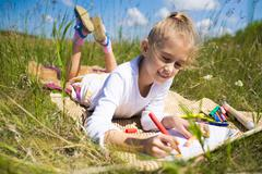 Portrait of cute girl with fair hair lying on grassland and drawing Stock Photos