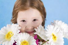 portrait of cute girl looking from behind spring flowers on blue background - stock photo