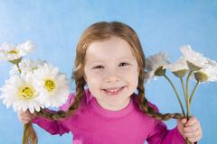 Stock Photo of portrait of joyful girl holding her pigtails and flowers in both hands